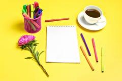 Il blocco note, fiori dell'aster, ha colorato i pennarelli, tazza con caffè su fondo giallo Autunno di concetto, estate, molla Fotografia Stock Libera da Diritti