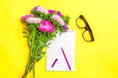 Il blocco note, fiori dell'aster, ha colorato i pennarelli, tazza con caffè su fondo giallo Autunno di concetto, estate, molla Fotografie Stock Libere da Diritti