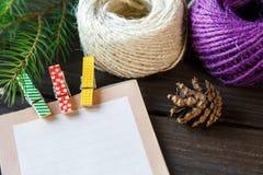 Il blocco note mette sui precedenti di legno per fare una lista per fare le cose o la lista dei presente per gli amici e la famig fotografia stock libera da diritti
