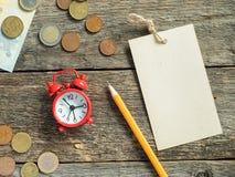 Il blocco note rosso della sveglia per la scrittura a matita di euro soldi conia sulla tavola rustica di legno Fotografia Stock