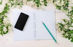 Il blocco note, il telefono e la matita con la molla selvaggia fiorisce Fotografia Stock Libera da Diritti