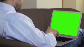Il blogger adulto che si siede sul sofà e sull'articolo nuovo di battitura a macchina sul computer portatile, freelance lavoro archivi video