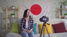 Il blogger della giovane donna nella camicia sui precedenti della bandiera del Giappone registra un video archivi video