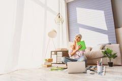 Il blogger femminile allegro è soddisfatto con le cose di studio Fotografia Stock