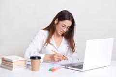 Il blogger femminile porta la camicia bianca, occhiali rotondi, scrive le note in blocco note, impianti sul computer portatile, c fotografia stock libera da diritti