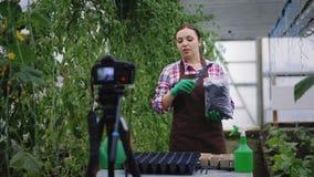 Il blogger femminile sta registrando il video circa il giardinaggio per il suo vlog stock footage