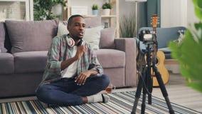 Il blogger popolare dell'uomo afroamericano allegro sta registrando il video per il suo blog online che parla e che gesturing l'e stock footage