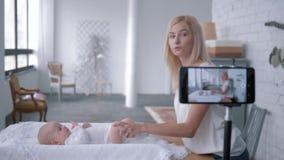 Il blogging, mamma fa la ginnastica per la bambina durante la registrazione del video d'istruzione nel flusso continuo da vivere  archivi video