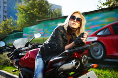 Il Blonde si siede circa un motociclo rosso Fotografie Stock