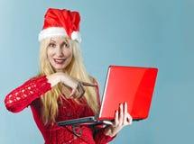 Il blonde in un cappello di nuovo anno s e con il computer portatile Fotografia Stock