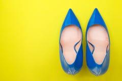 Il blu alla moda ha laccato le scarpe su un fondo giallo luminoso Fotografia Stock