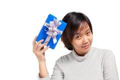 Il blu asiatico della tenuta dei capelli di scarsità della donna ha avvolto il regalo Fotografia Stock Libera da Diritti