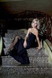 Il blu biondo ha osservato, modello del fascino con il vestito da sera nero Fotografia Stock