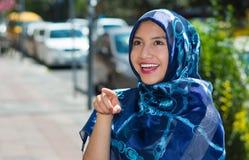 Il blu d'uso della bella giovane donna musulmana ha colorato il hijab, indicante il dito che sorride, all'aperto fondo urbano Immagini Stock