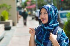 Il blu d'uso della bella giovane donna musulmana ha colorato il hijab, indicante il dito che sorride, all'aperto fondo urbano Fotografie Stock Libere da Diritti
