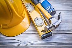Il blu del casco della costruzione del martello da carpentiere ha rotolato il raggiro dei disegni di ingegneria Immagini Stock Libere da Diritti
