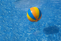 Il blu di giallo arancio ha colorato la palla in uno stagno con acqua blu Immagini Stock Libere da Diritti