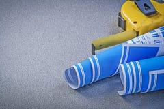 Il blu di misurazione del nastro ha rotolato i disegni di ingegneria sul backgrou grigio Fotografie Stock Libere da Diritti