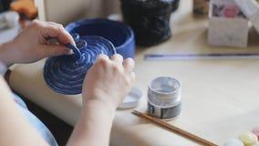 Il blu femminile della vernice dell'artista ha dipinto il secchio fatto a mano decorato con una spazzola stock footage