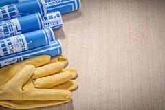 Il blu ha rotolato i guanti di cuoio della sicurezza dei disegni di costruzione su woode Fotografie Stock Libere da Diritti