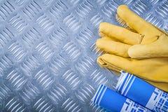 Il blu ha rotolato i guanti protettivi del cuoio dei disegni di ingegneria sul co Immagine Stock