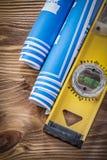 Il blu ha rotolato il livello della costruzione dei disegni di ingegneria sulla BO di legno Fotografie Stock Libere da Diritti