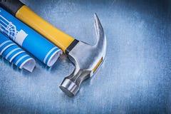 Il blu ha rotolato il martello da carpentiere dei disegni di ingegneria sul backgro metallico Fotografie Stock