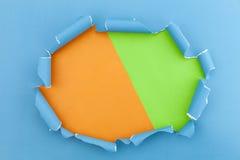 Il blu ha strappato la carta aperta su fondo di carta verde ed arancio Fotografia Stock