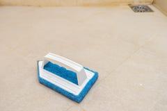 Il blu sfrega la spazzola sul pavimento del bagno immagini stock libere da diritti