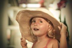 Il blu sorridente ha osservato la bambina bionda che tiene il suo grande cappello Immagine Stock