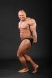 Il Bodybuilder dimostra le braccia ed i muscoli dei piedini Immagini Stock