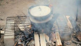 Il bollitore sul fuoco di accampamento è caldo video d archivio
