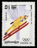 Il bollo stampato in Cambogia mostra l'immagine del saltatore di sci occasionalmente dei giochi olimpici a Sarajevo Immagine Stock Libera da Diritti