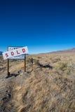 Il bordo del segno che dice una terra dell'azienda agricola è stato venduto nel deserto di nev Immagini Stock Libere da Diritti
