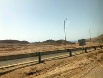 Il bordo della strada, la strada principale con asfalto nel deserto con la sabbia, paraurti e pali della luce, dune di sabbia, co fotografia stock