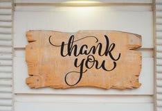Il bordo di legno in bianco sulla parete ed il testo vi ringraziano Tiraggio della mano dell'iscrizione di calligrafia Immagine Stock
