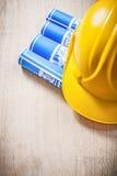 Il bordo di legno con il blu ha rotolato il casco di sicurezza dei disegni di ingegneria Immagine Stock