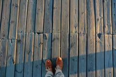 Il bordo di legno leggero anziano con la struttura visibile buona di legno e con stare sulla sua arancia maschio delle gambe boot Immagini Stock Libere da Diritti