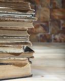 Il bordo di una pila di vecchi libri sdraiati su una tavola di legno Primo piano Fotografie Stock