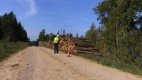 Il boscaiolo ha messo i coni della strada sulla strada rurale vicino al mucchio del ceppo archivi video