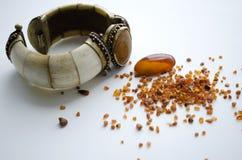Il braccialetto d'annata delle donne fatto di avorio e decorato con il chalcedony accanto ad ambra Immagine Stock