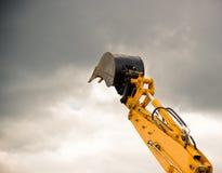 Il braccio arancione pesante dell'escavatore raggiunge il cielo Immagini Stock