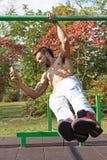 Il braccio bello del maschio uno tira sull'allenamento ed il telefono di Smat facendo uso di Esercizi di allenamento della via Fotografia Stock