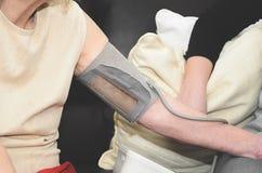 Il braccio dell'gli anziani ha allungato, wraped con un monitor di pressione sanguigna Immagini Stock Libere da Diritti