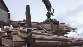 Il braccio della gru scarica le rimanenze del legname dal camion alla segheria stock footage
