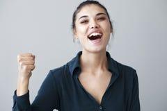 Il braccio felice della donna ha sollevato la mano su backgorund grigio Fotografie Stock