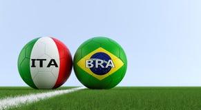 Il Brasile contro Partita di calcio dell'Italia - palloni da calcio nei colori nazionali di Brazils e di Italys su un campo di ca Fotografia Stock Libera da Diritti