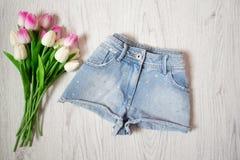 Il breve denim mette con i cristalli di rocca, tulipani rosa Concetto alla moda, vista superiore Fotografia Stock Libera da Diritti