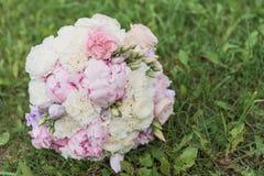 Il bride& x27; mazzo di s Suona le persone appena sposate Un mazzo dei fiori con gli anelli immagine stock
