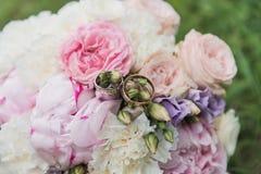Il bride& x27; mazzo di s Suona le persone appena sposate Un mazzo dei fiori con gli anelli fotografie stock